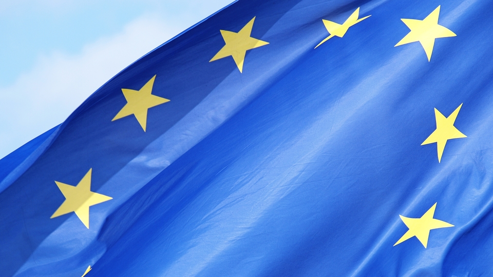 a shot of the european flag on bright blue sky
